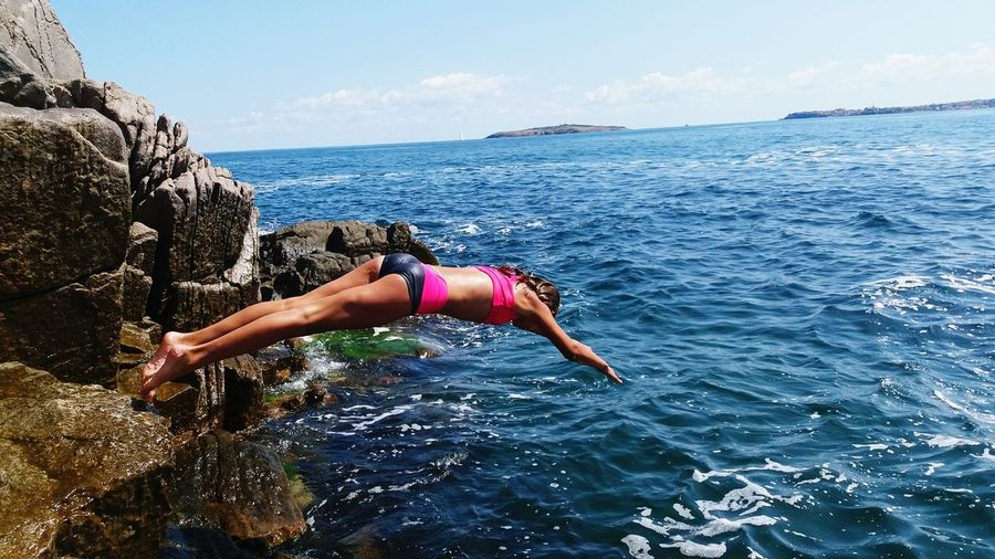 Woman Diving Into Sea Against Sky
