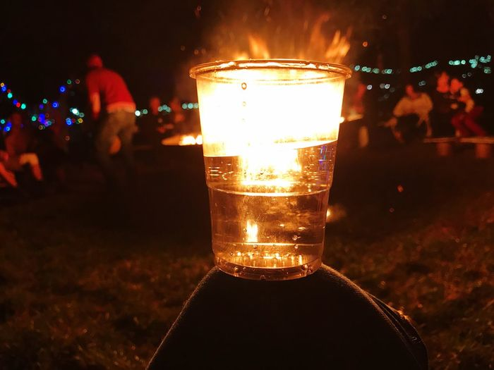 Night Illuminated Alcohol Drink Focus On Foreground Drinking Glass Beer Beer Glass Close-up Real People Food And Drink One Person Celebration Human Hand Outdoors People In The Background Human Body Part Freshness People Campfire