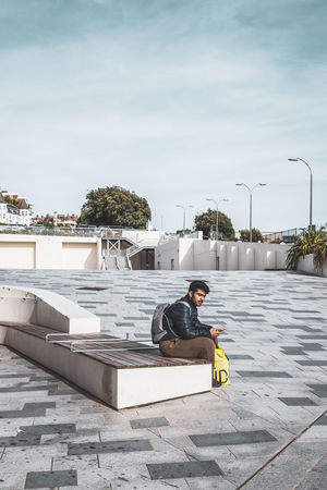 one person sitting alone EyeEm Best Shots Architecture Building Exterior Built Structure Casual Clothing Day Full Length Leisure Activity Lifestyles Nature One Person Outdoors Plant Real People Relaxation Sitting Sky Street Photography Swimming Pool Urban Landscape Water Young Adult Young Men