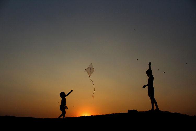 Silhouette Children Flying Kite Against Clear Sky During Sunset