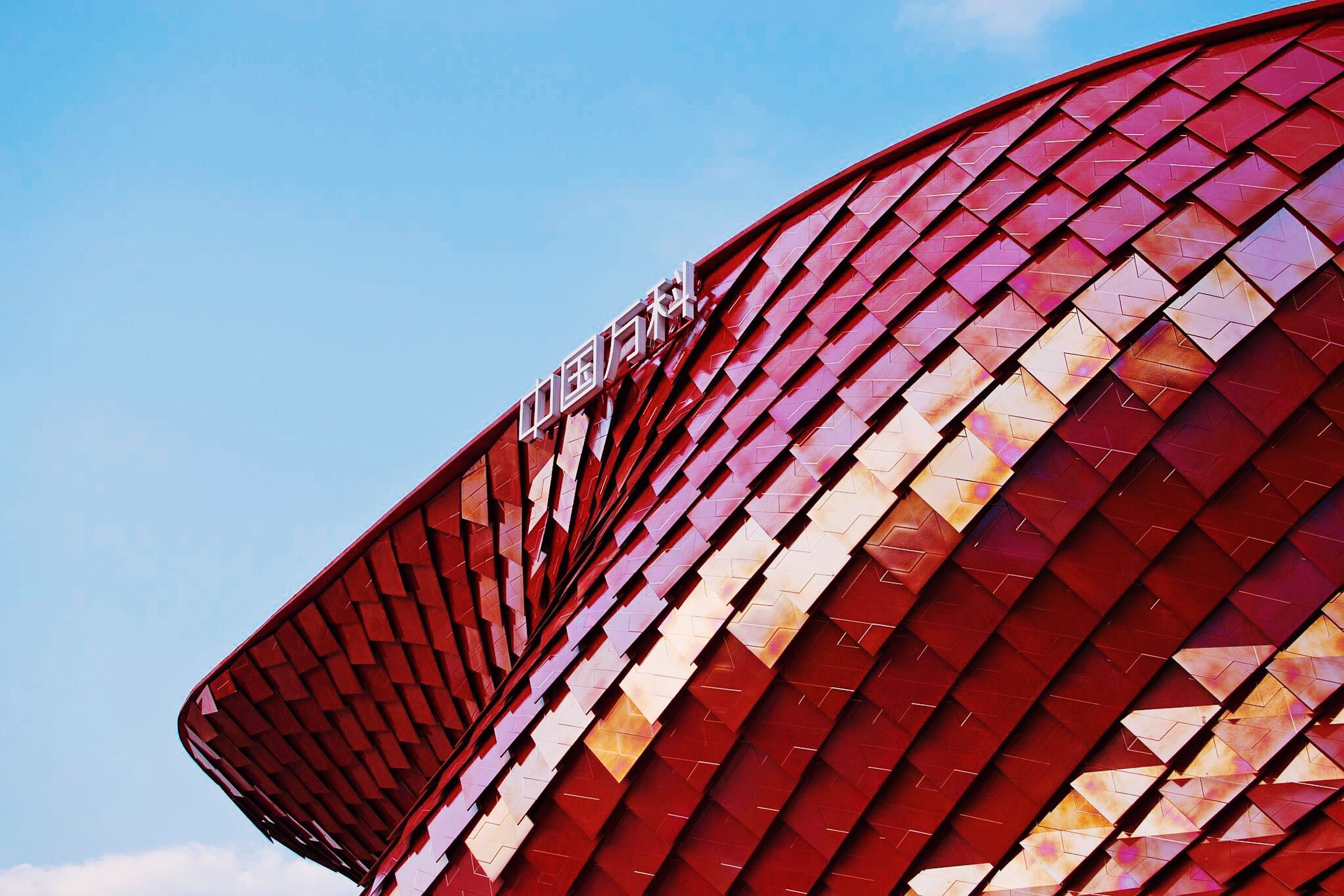 architecture, built structure, building exterior, low angle view, clear sky, red, sky, blue, outdoors, flag, day, city, modern, part of, high section, no people, pattern, national flag, patriotism, building
