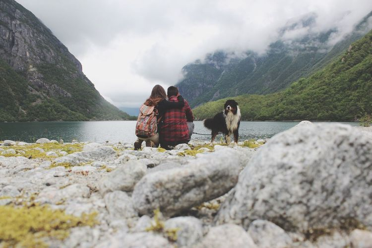 People crouching by dog against mountain