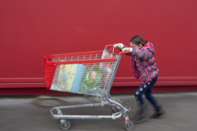 Cart Red Red Color Red Cart Shopping Cart Full Length One Person Retail  Consumerism Pushing Shopping Blurred Motion Store Supermarket Adult Motion Young Adult Groceries Side View Casual Clothing Customer  Buying Red Background Motion Blur Fun Streetwise Photography