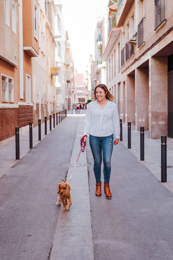 Woman walking with dog on street in city
