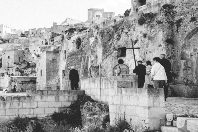 Rear view of people on wall against historic building