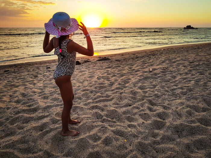 Side view of girl wearing hat standing at beach during sunset