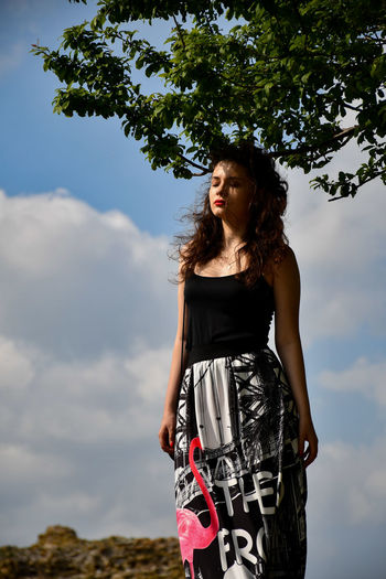 Beautiful young woman standing against sky
