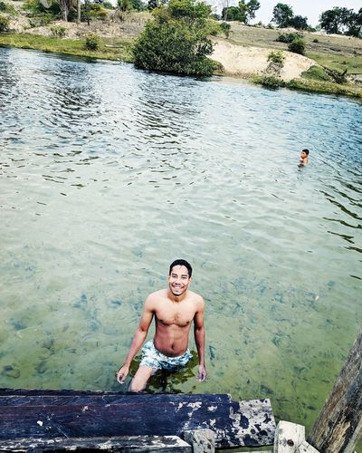 High angle portrait of shirtless man standing in lake