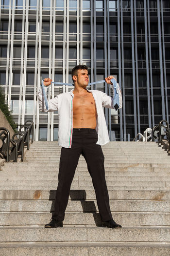 Man wearing fully unbuttoned shirt while standing on steps