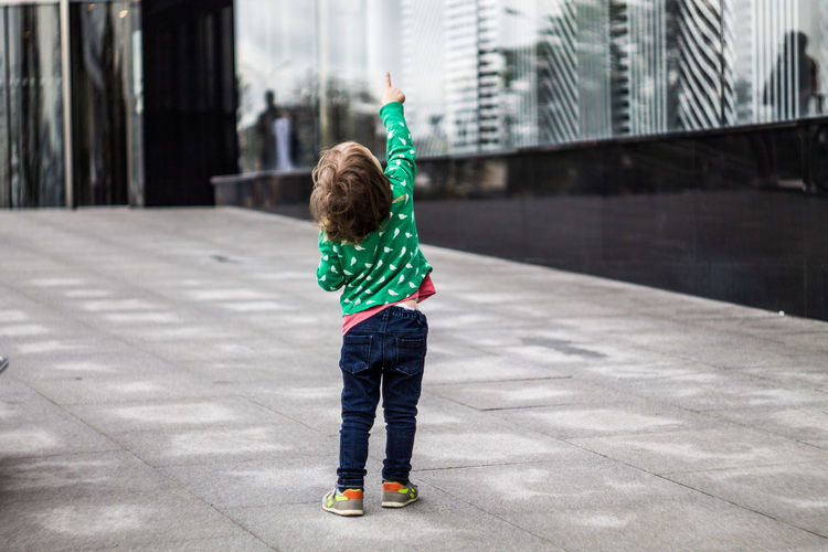Architecture Arms Raised Building Exterior Built Structure Casual Clothing Child Childhood City Day Focus On Foreground Hand Raised Human Arm Innocence One Person Outdoors Real People Rear View Standing