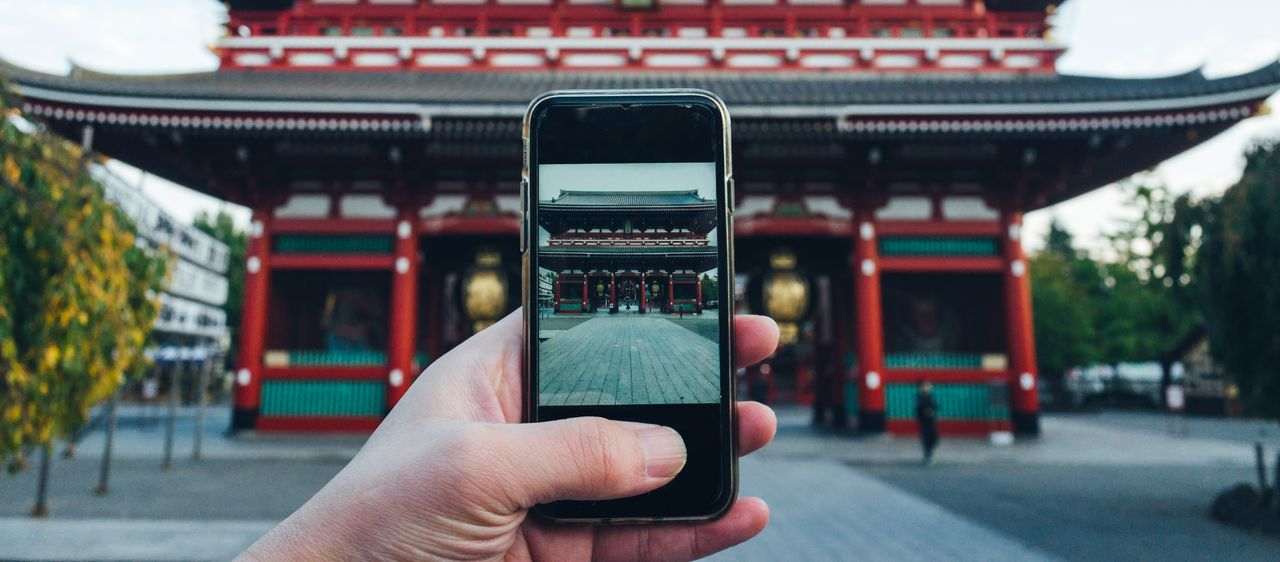 Close-up of cropped hand photographing temple with smart phone