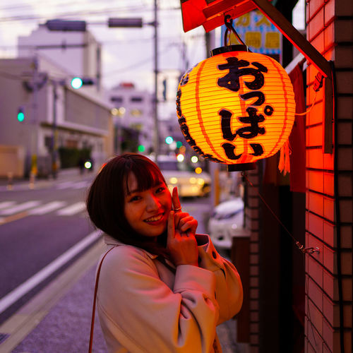 Portrait of woman smiling in illuminated city at night