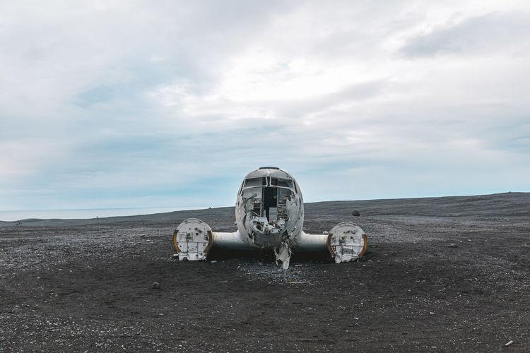 Abandoned machinery on land against sky