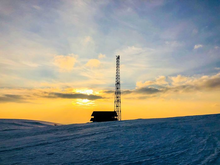 Silhouette of house and power transmission tower at sunset in winter Mountain Electricity  Tower Chalet Cabin House Reflection Sunrays Sun Golden Hour Dusk Frozen Cold Snow Winter Cloud - Sky Sky Sunset Nature Architecture Silhouette Built Structure Beauty In Nature Scenics - Nature No People Technology Orange Color Fuel And Power Generation Horizon Outdoors