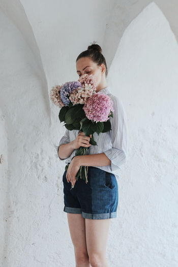 Young Woman Holding Bouquet Against Wall