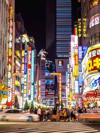 People on city street amidst illuminated buildings at night