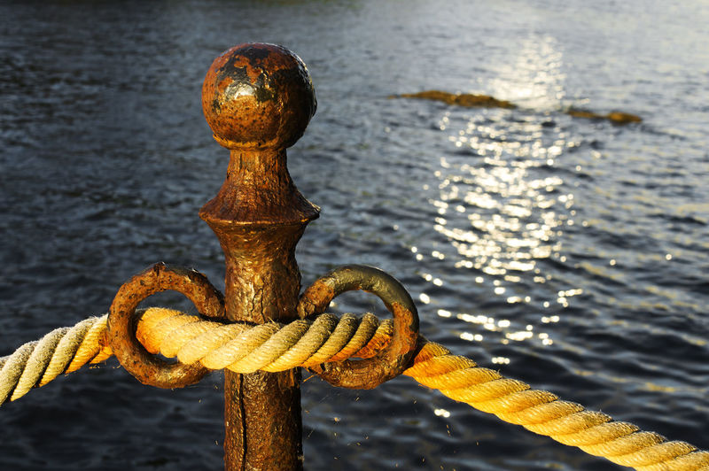 Close-up of rope attached to bollard against sea