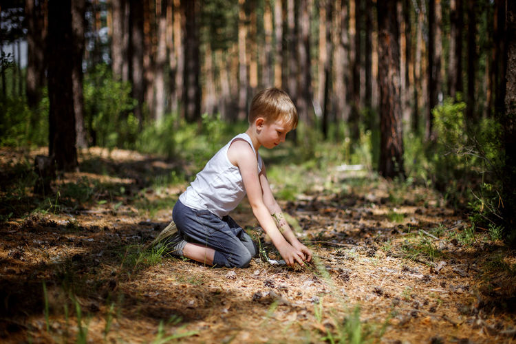 Side view of boy in forest