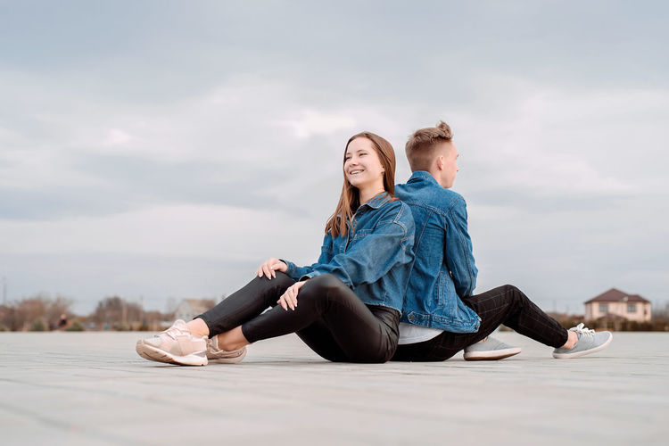 Young loving couple wearing jeans sitting back to back in the street spending time together