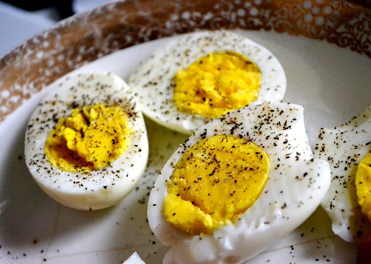 High angle view of pepper on boiled eggs in plate