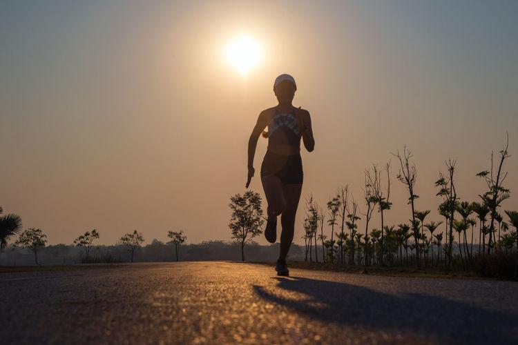 Full length of woman running on road
