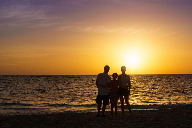 Silhouette friends on beach against sunset sky