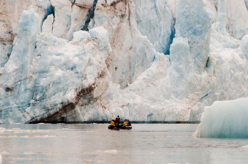 People On Raft In Sea Against Glacier