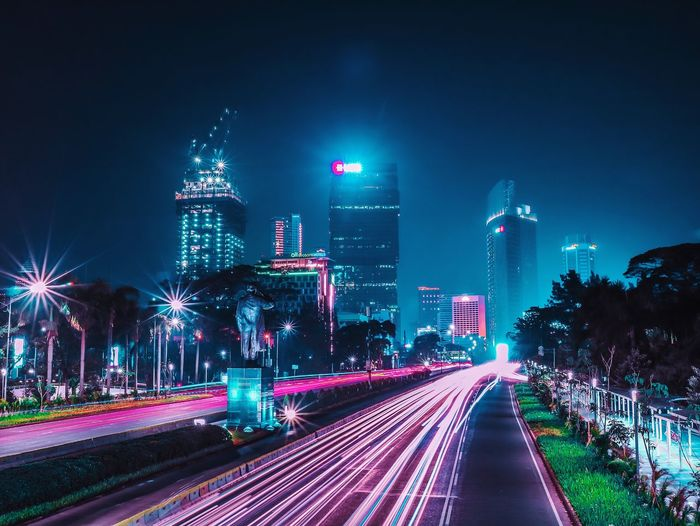 Light trails on road amidst illuminated buildings against sky at night