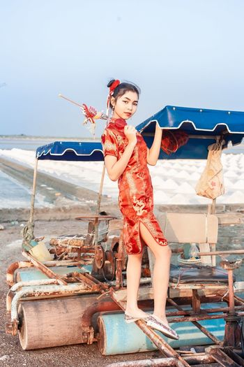 Full length of women in chinese culture costume standing on beach against sky