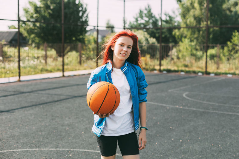 Portrait of a smiling teenage girl with a basketball on the sports field. sports, health, lifestyle