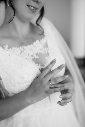 Midsection of bride wearing ring in finger