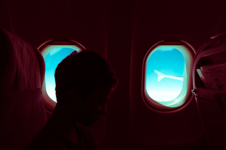 Midsection of man sitting in airplane at night