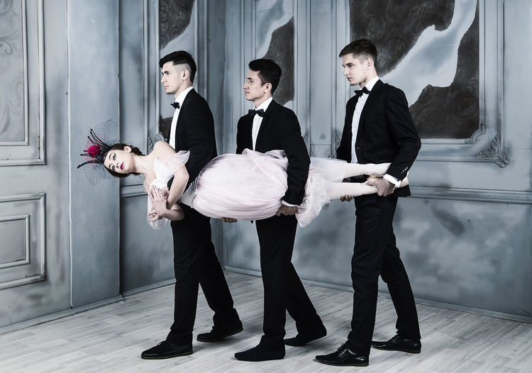 Well-dressed men carrying ballet dancer while walking on floor