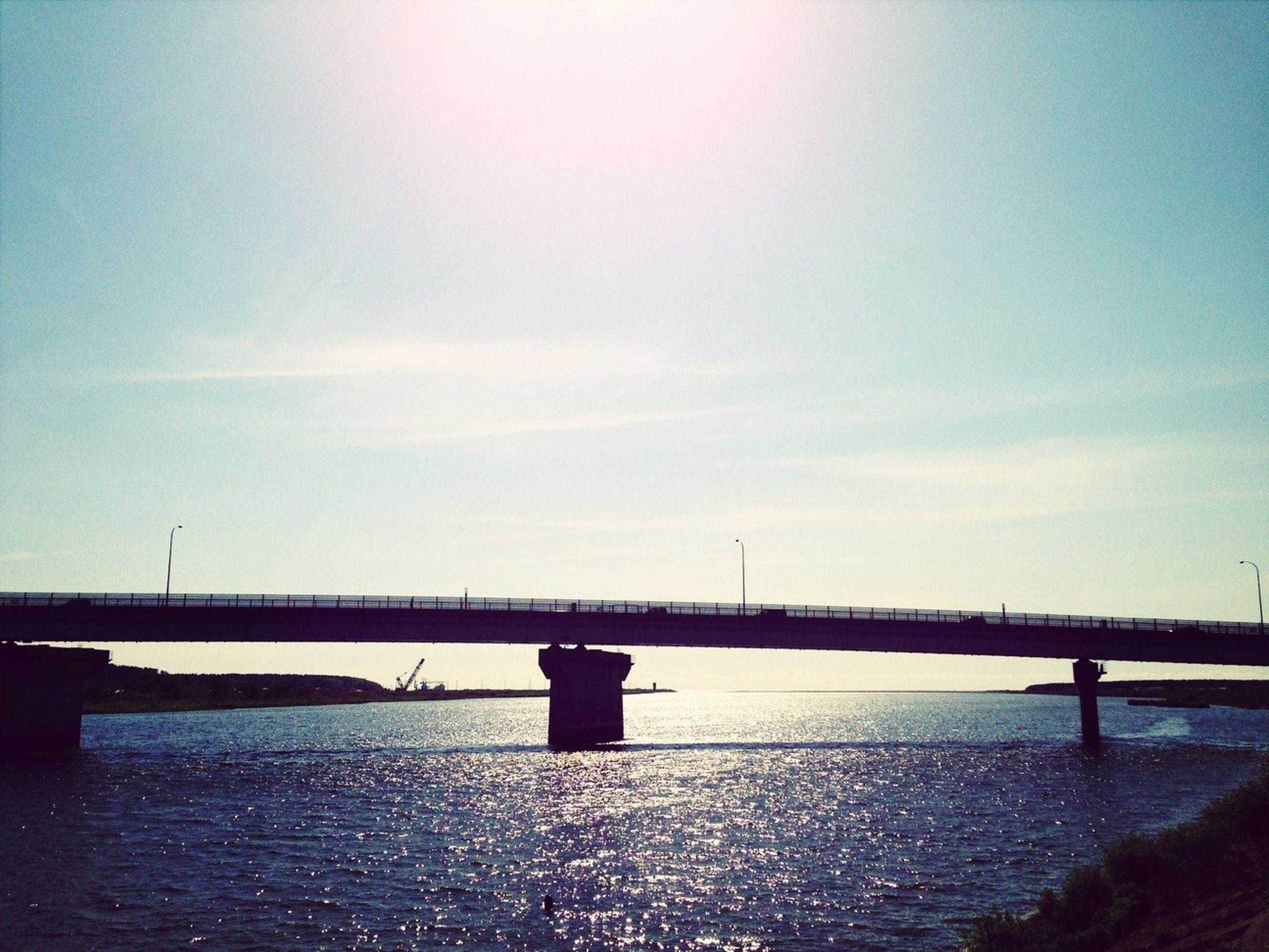 connection, bridge - man made structure, built structure, water, architecture, bridge, river, sky, engineering, waterfront, transportation, rippled, suspension bridge, cloud - sky, tranquility, long, sea, nature, railing, cloud