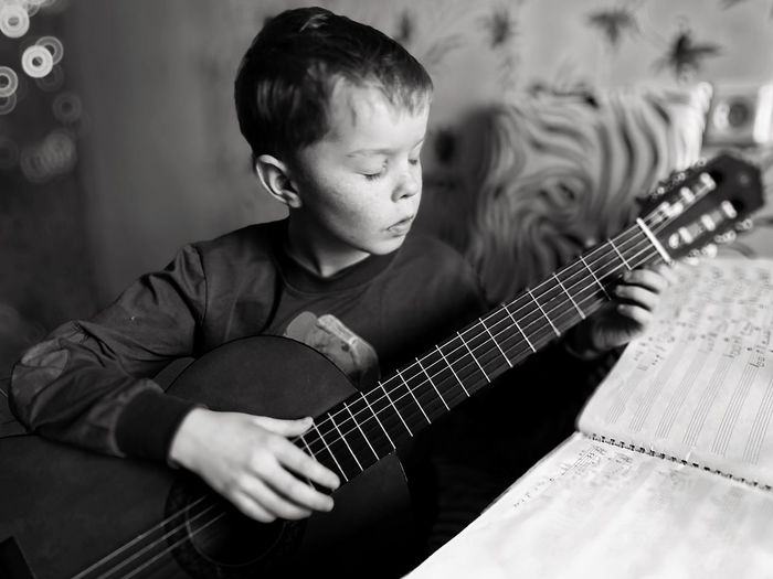 Boy playing guitar at home