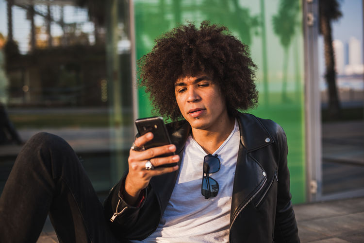 Young man using mobile phone outdoors
