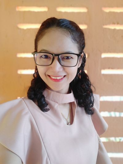 Portrait of smiling businesswoman in eyeglasses against wall