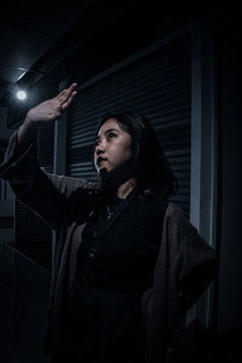 Young woman with hand raised while standing in dark