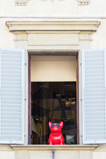 Red toy car on window of building