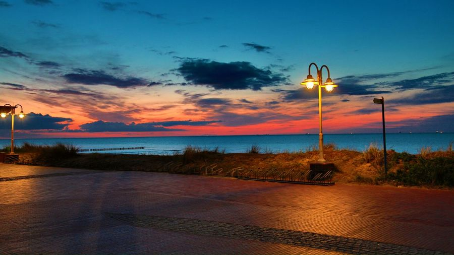Street light by sea against sky at sunset