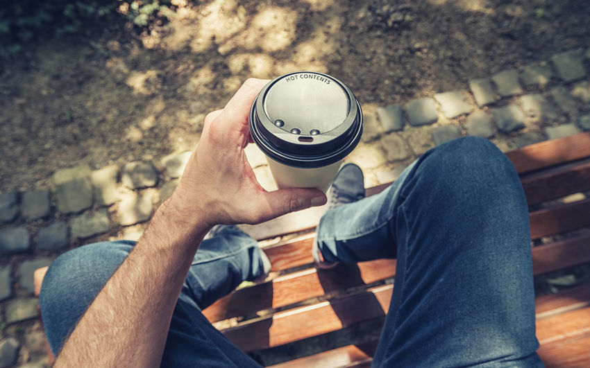 man holding a coffee mug and sits on a park bench at summer Beverage Coffee Coffee Time Park Bench Shadows & Lights Break Casual Clothing Close-up Coffee To Go Day High Angle View Holding Human Body Part Human Hand Human Leg Lifestyles Low Section Men Mug One Person Outdoors People Real People Sitting Summer