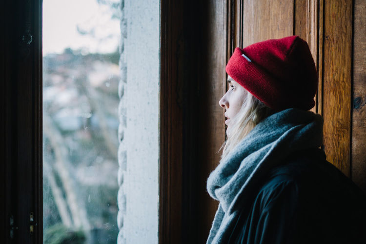 Young woman looking through window in winter