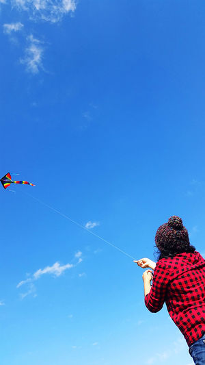 Low Angle View Of Woman Flying Kite Against Blue Sky