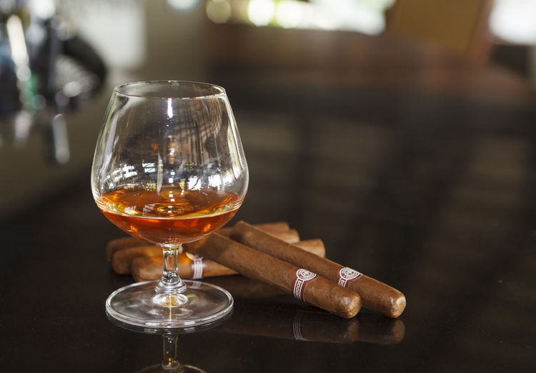 Close-Up Of Whiskey In Glass By Cigars On Table In Restaurant