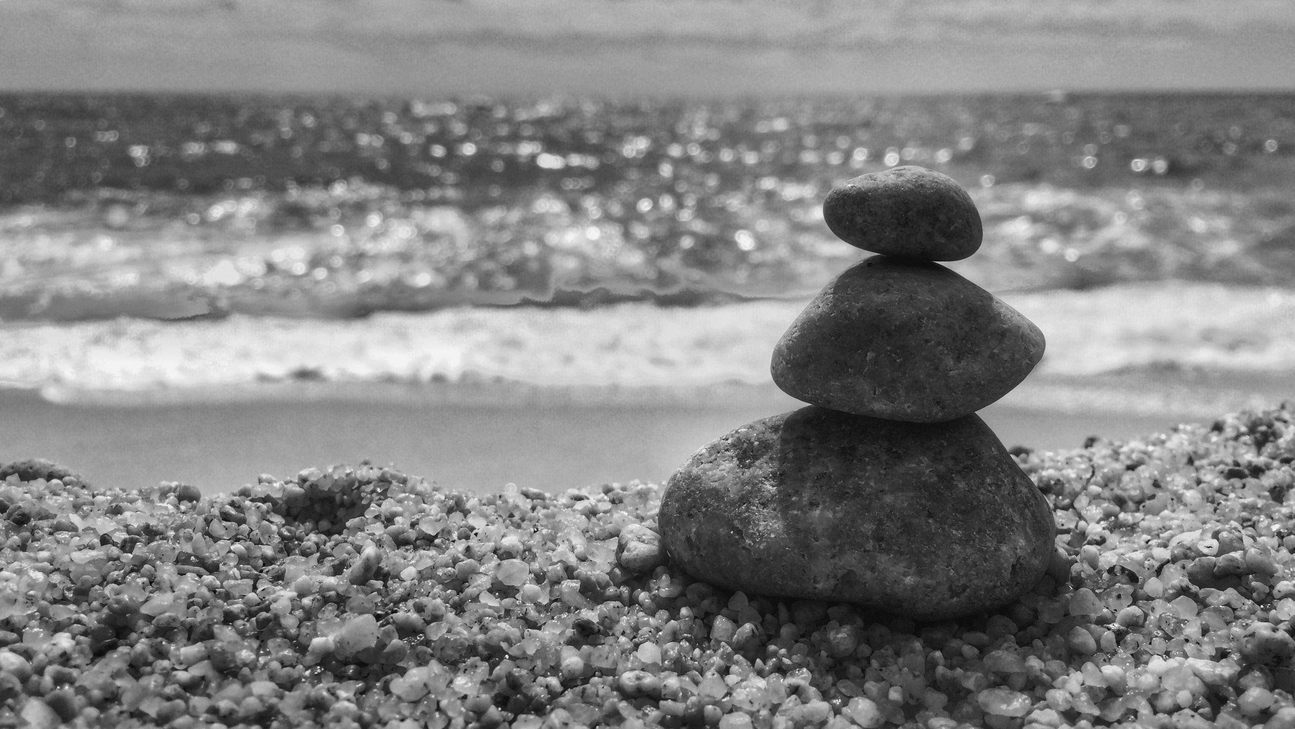 sea, pebble, rock - object, tranquility, beach, tranquil scene, water, stone - object, nature, focus on foreground, horizon over water, shore, beauty in nature, sky, scenics, stone, close-up, rock, stack, day