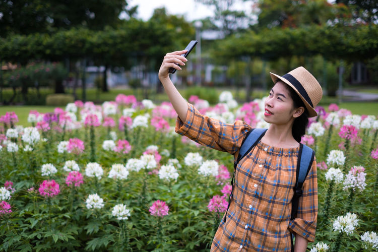Young Woman Taking Selfie By Flowers At Park