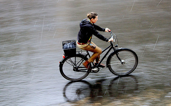 a young woman is driving with her bike through the rain Alone Bicycle Bicycles Calmity Celebrate Your Ride Cycling Driving Fahrrad Frau Fun Lifestyle Motion Rain Raniy Days Real People Reflection Reflections In The Water Regen Riding Street Woman