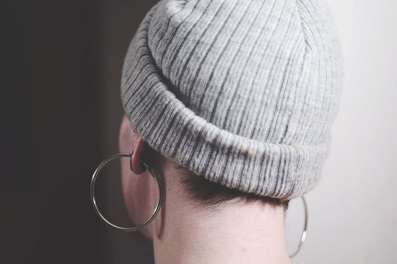 Close-up of woman wearing earrings and hat