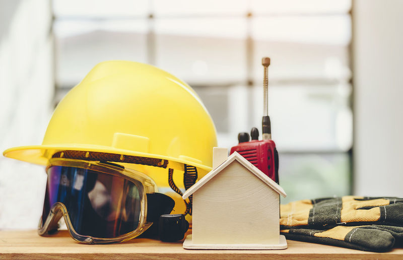 Close-Up Of Protective Workwear With Walkie-Talkie By Model Home On Table