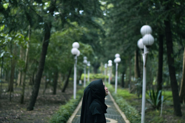 Side view of woman wearing hijab standing on footpath in park